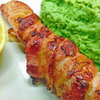 Salmon wrapped with streaky bacon and served with mushy peas